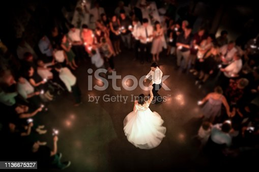 Top view on a wedding couple dancing the opening waltz at their wedding celebration. All their friends are standing in a ring around them with a light in their hands. Focus only on the bridal couple.