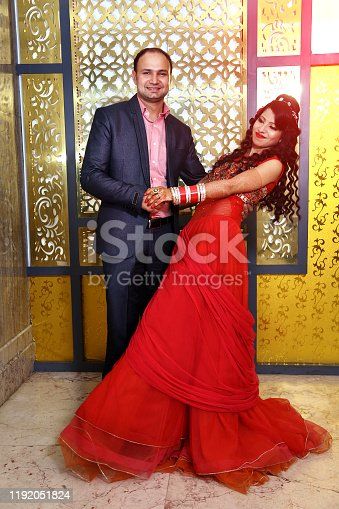 Young wedding couple of Indian ethnicity dancing together in the reception party hall.