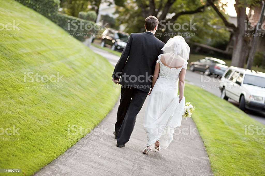 Wedding Couple Departing for Honeymoon Holding Hands royalty-free stock photo
