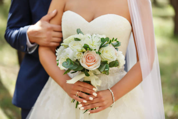 Wedding couple, groom and bride holding wedding bouquet of fresh flowers. Marriage concept stock photo