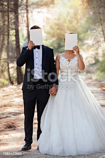 istock Wedding couple hiding face with blank paper. 1083443668