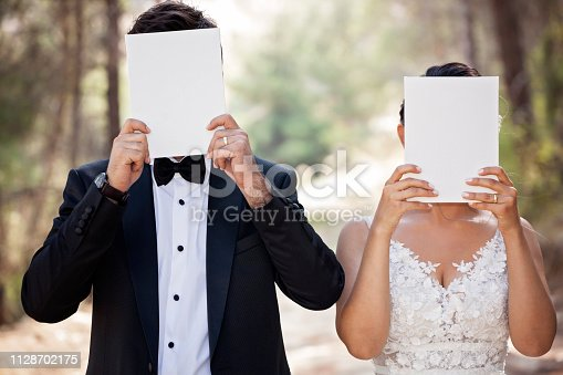 istock Wedding couple hiding face with blank paper. 1128702175
