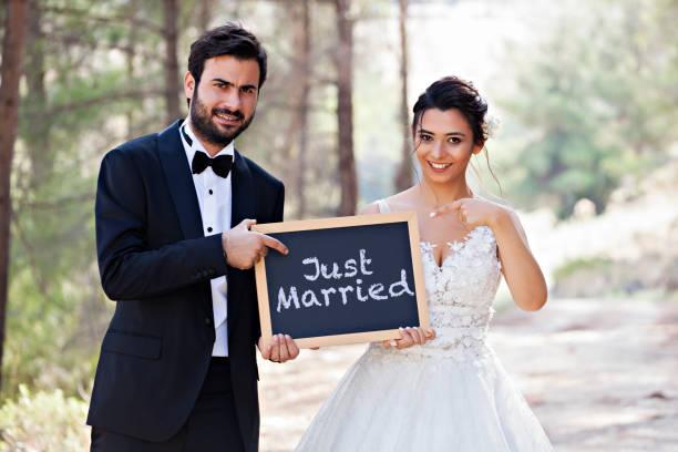 hochzeitspaar mit einer tafel. gerade geheiratet. - heiratssprüche stock-fotos und bilder