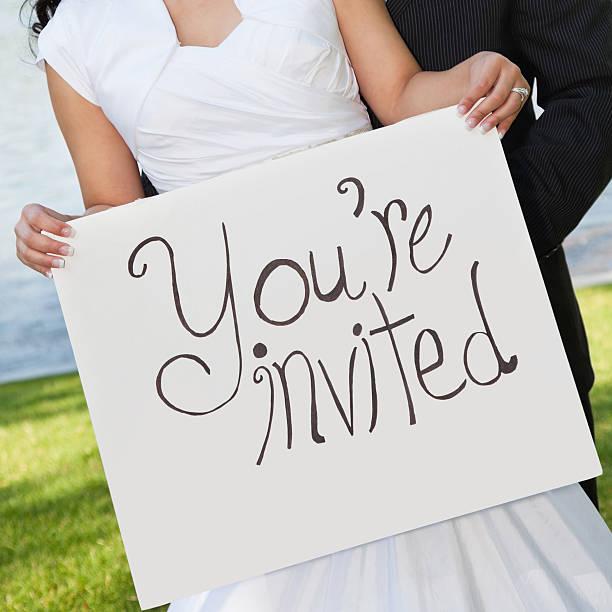 hochzeit paar holding du bist eingeladen - verlobungsfeier einladungen stock-fotos und bilder