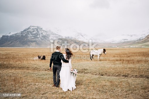 Wedding couple in after with horses. The groom hugs the bride.