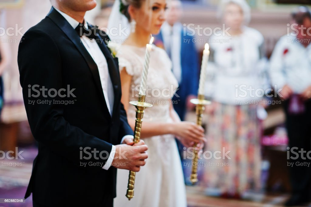 Wedding couple in church with burning candle at candlestick on hands. stock photo