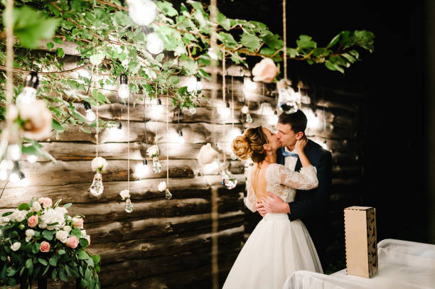 Wedding couple in magical night forest decorated light garlands. Ceremony with lanterns and lamps decorated flowers. Bride and groom kissing on background of bulb lights.