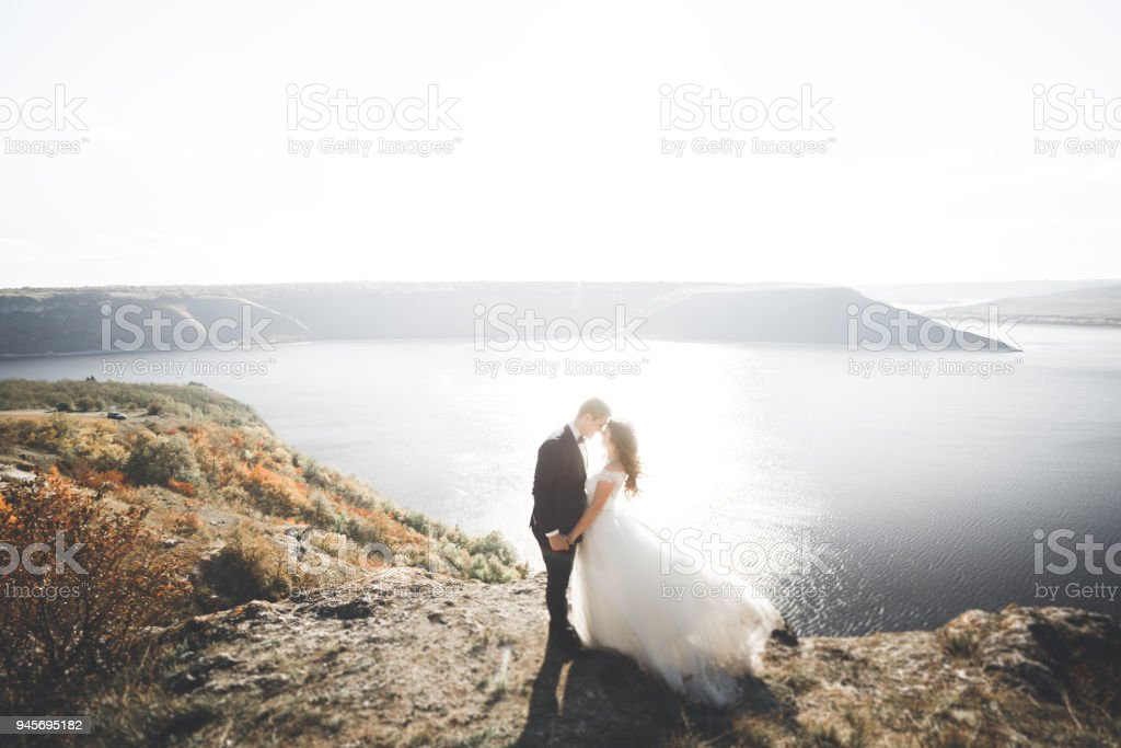 Wedding couple kissing and hugging on rocks near blue sea stock photo