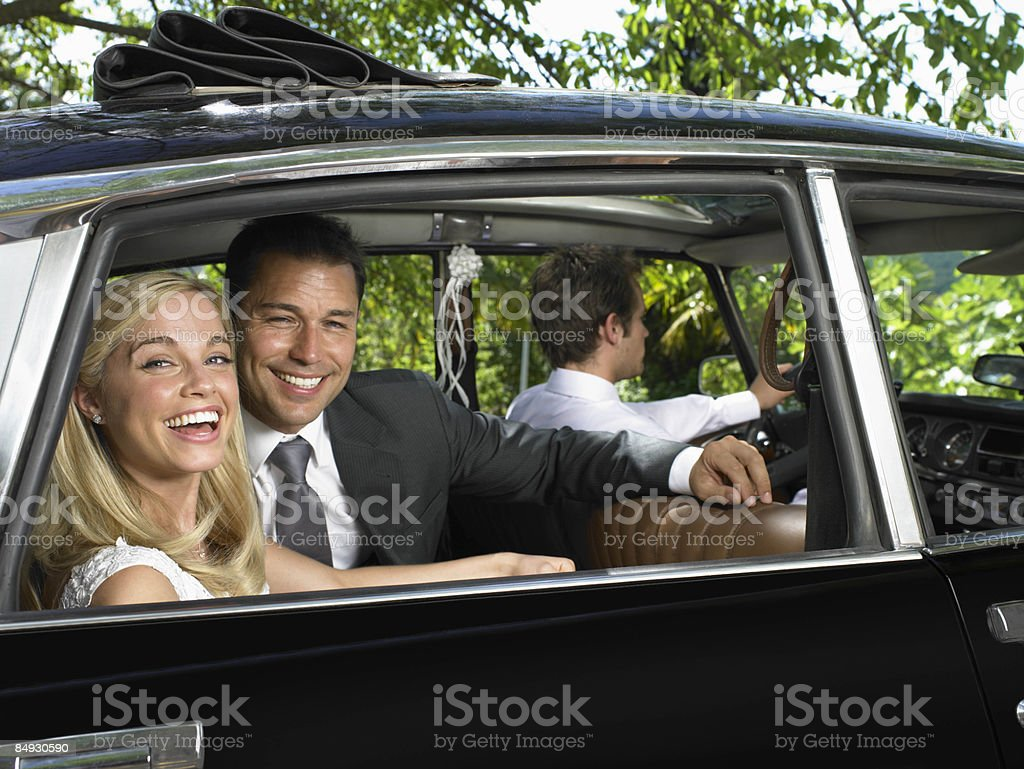 Wedding couple laughing in car stock photo