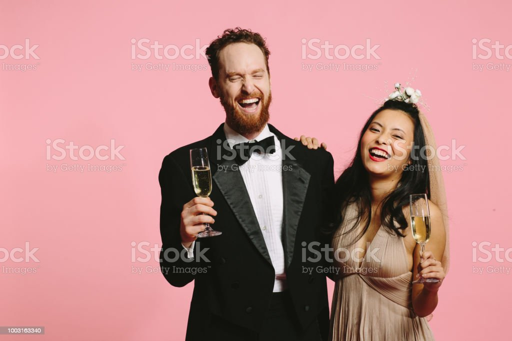 Wedding couple laughing out loud and holding champagne stock photo