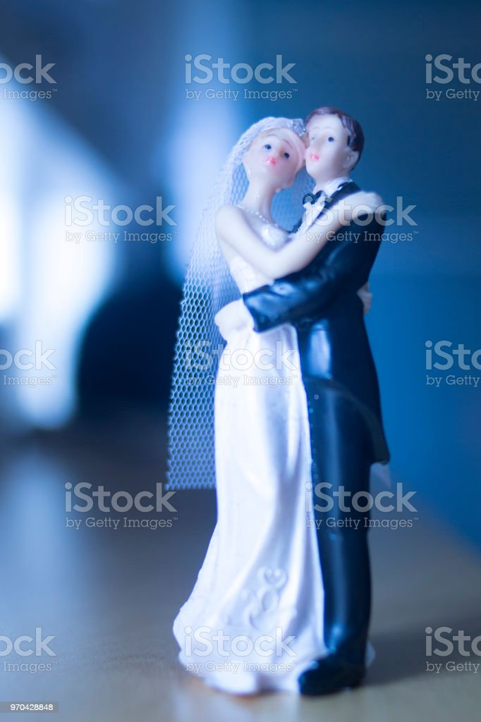 Wedding couple marriage cake topper plastic figures with tuxedo evening suit, white weddding dress veil. stock photo