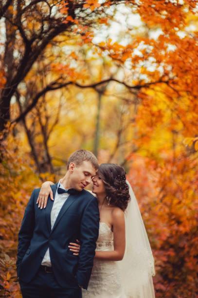 Wedding couple on a walk in the autumn park stock photo