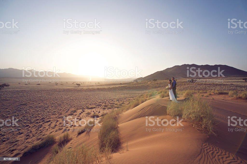 Wedding Couple on sand dune at sunset stock photo