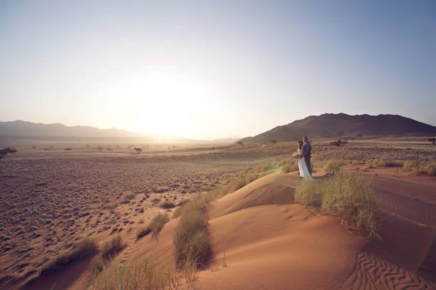 hochzeitspaar auf sanddüne bei sonnenuntergang - namib wüste stock-fotos und bilder