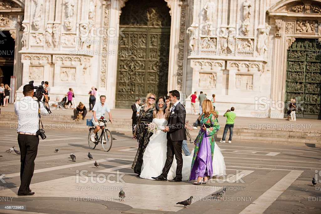 Wedding Couple posing to videographer at Duomo, Milan, Italy royalty-free stock photo