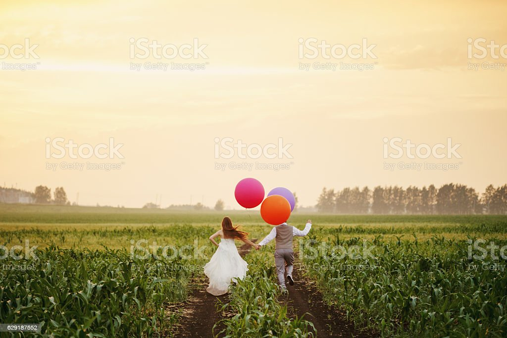 Wedding couple running away on the field stock photo