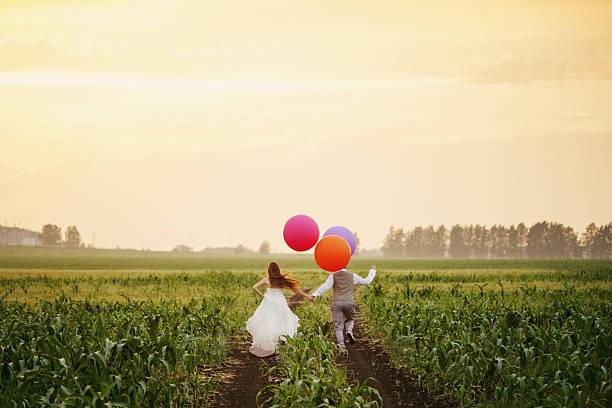 Wedding couple running away on the field – Foto