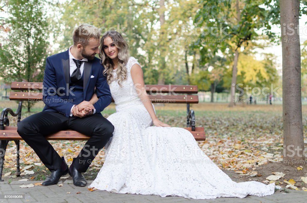 Wedding couple sitting on the bench stock photo