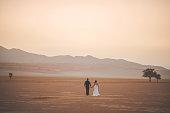Married heterosexual couple standing in open desert scene with sand dune and trees Wolwedans Namib Rand Namibian Desert Namibia Africa