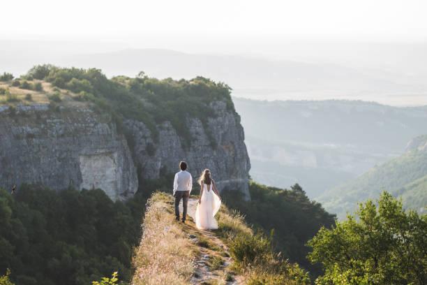 hochzeitspaar, wandern in den bergen mit herrlichem ausblick - hochzeitsreise ohne mann stock-fotos und bilder
