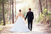 Walk of love in the nature. Wedding couple walking on road in a forest.