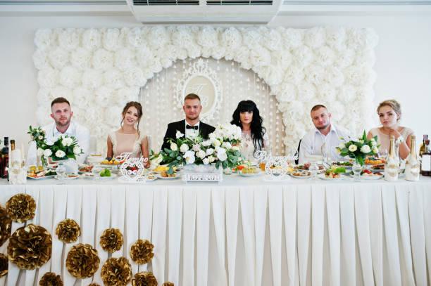 brautpaar mit trauzeugen und brautjungfer auf tisch im restaurant. - bräutigam tisch stock-fotos und bilder