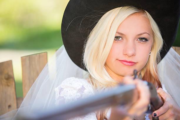 hochzeit: cowboy hochzeit tag braut in mütze holding antike gewehr. - shotgun wedding stock-fotos und bilder