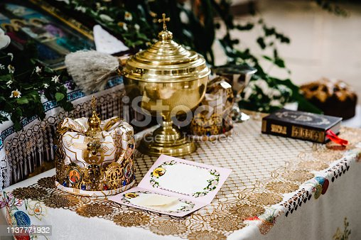 Wedding crowns in church ready for marriage ceremony. close up. Bible, crown, bowl, Certificate of the glans in the church on table. Place for text.