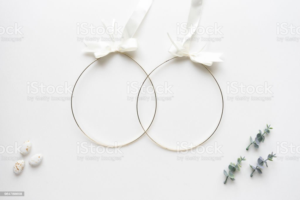 Wedding crowns, oregano branches and candy on white marble. Top view. royalty-free stock photo