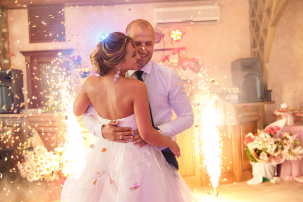 Wedding dance of bride and groom with special effects- colorful smoke and fireworks. Newlyweds couple dancing at wedding day. Marriage and wedding party concept stock photo