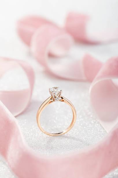 Wedding diamond ring on pastel background with pink ribbon stock photo