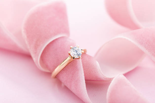 Wedding diamond ring on pastel background with pink ribbon