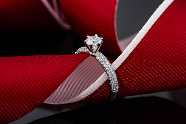 Wedding diamonds ring on black background with red ribbon stock photo