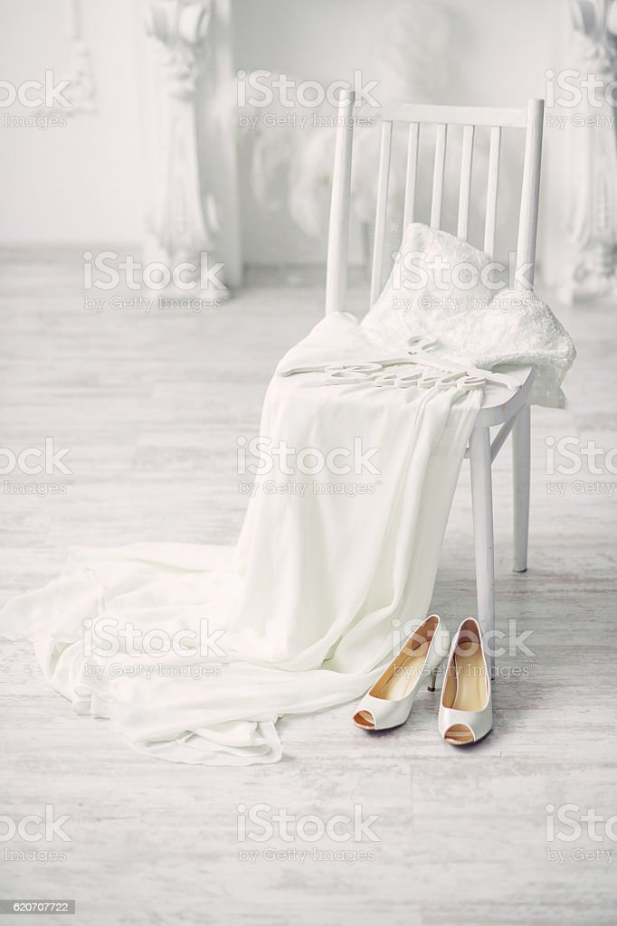 Wedding Dress And Shoes On A Chair In White Interior Royalty Free Stock  Photo