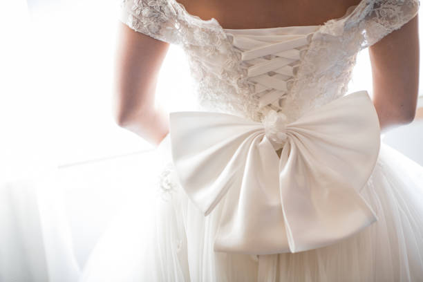 Wedding dress back detail. Close-up of brides beauty against white background stock photo