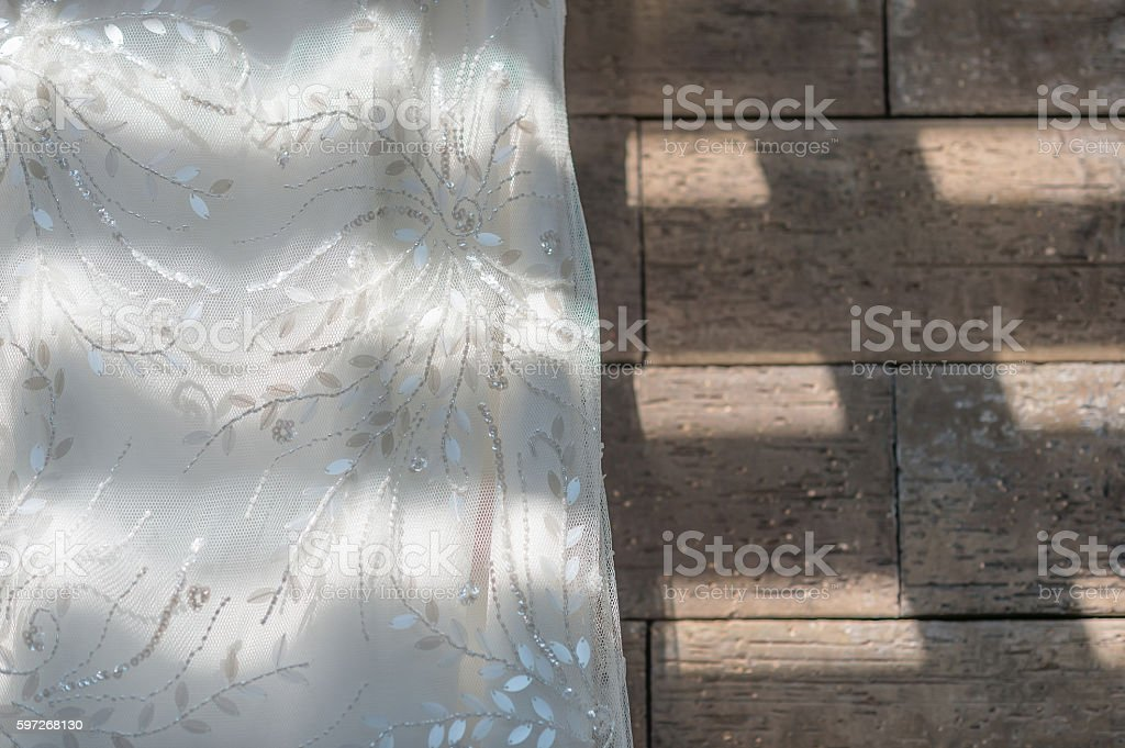 Wedding dress close up hanging on brown granite Lizenzfreies stock-foto