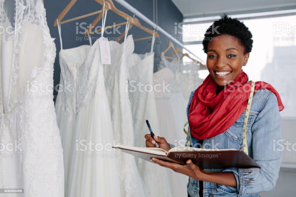 Wedding dress designer working in her boutique stock photo