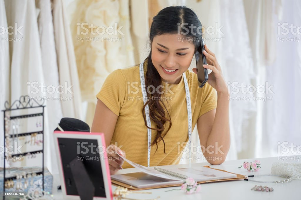 Wedding Dress Designer Working With Smart Phone In Wedding Salon Of Fashion Store Stock Photo Download Image Now Istock