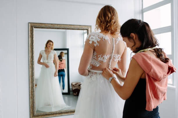 Wedding dress fitting in bridal boutique stock photo
