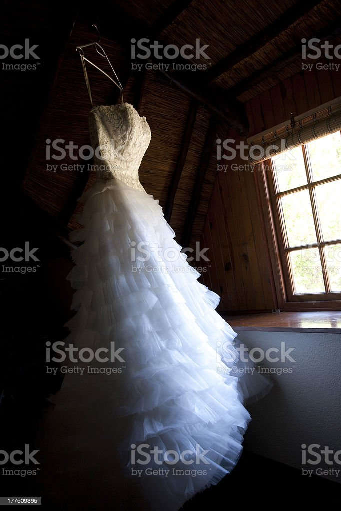 Wedding dress hanging at a window royalty-free stock photo