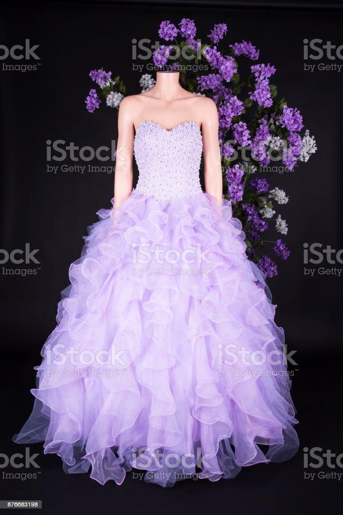 d94d80c3a1 Vestido de Novia de color lila sobre un maniquí sobre un fondo de flores  lilas foto
