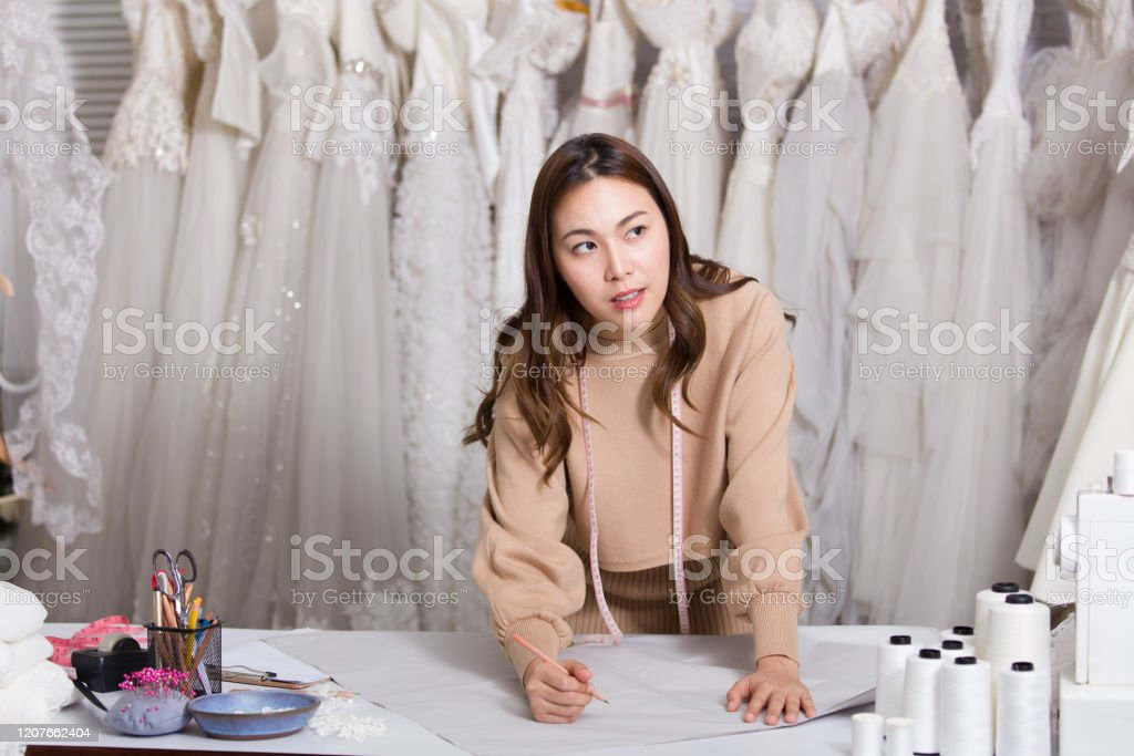 A Wedding Dress Rental Shop Owner Showing A Gesture Of Thinking To Design New Outfits For Clients Woman Dressmaker In Her Bridal Boutique Small Business Entrepreneur Concept Stock Photo Download Image
