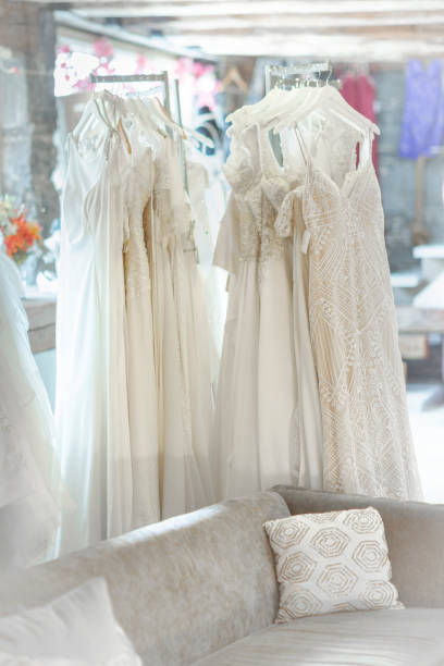 wedding dresses hanging at bridal shop - katiedobies stock pictures, royalty-free photos & images