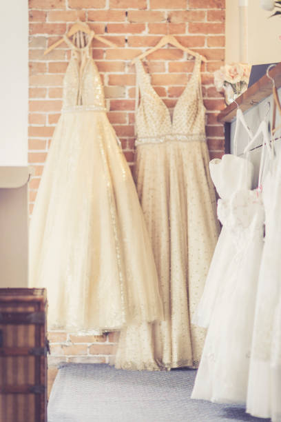 wedding dresses hanging at rustic bridal shop - katiedobies stock pictures, royalty-free photos & images