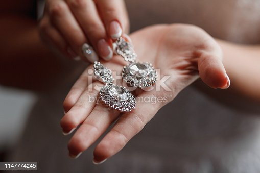 istock Wedding earrings on a bridal hand, bride's morning and jewelry accessories and decoration concept 1147774245