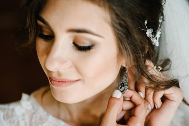 hochzeit ohrringe auf einer weiblichen handkleidung, nimmt sie die ohrringe, die brautgebühren, morgens braut, frau in weißem kleid. - ohrringe tropfen stock-fotos und bilder