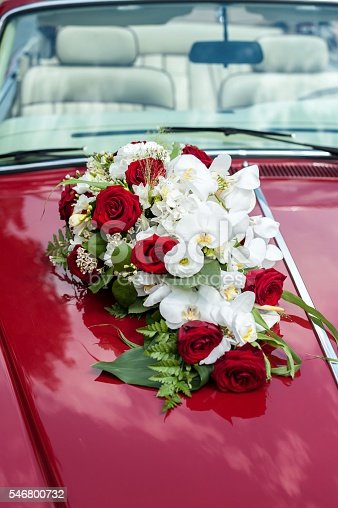 Vertical close-up image of beautiful bunch of roses with orchids attached on luxury red car, ready to transport on wedding ceremony. Elegant floral wedding decoration.