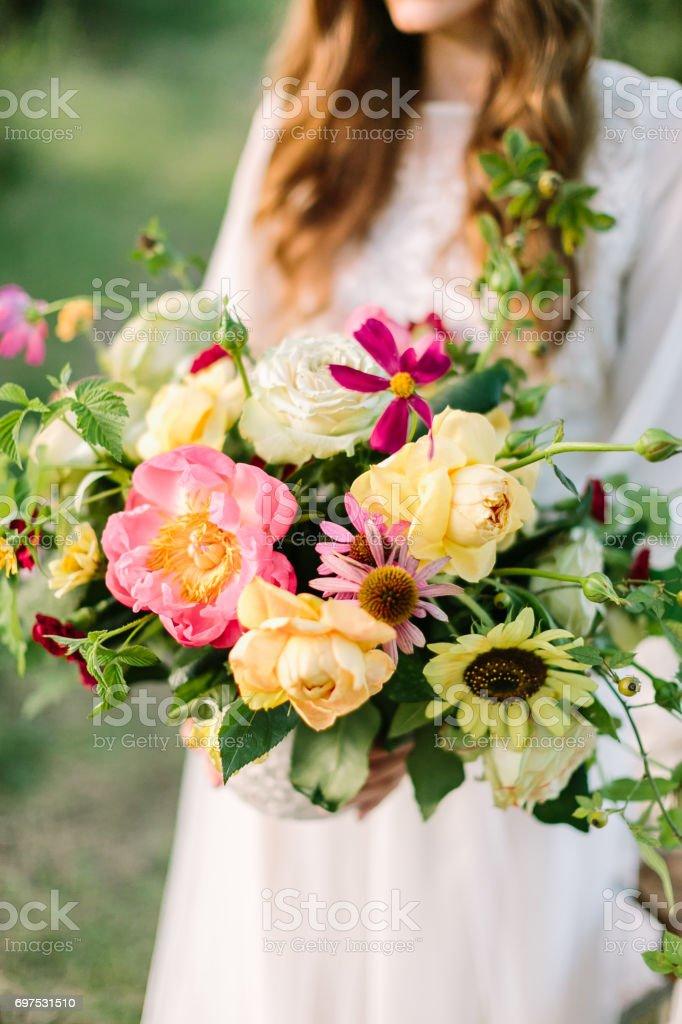 mariage, mode, design floral, concept célébration - beau bouquet d'avalanches tendres fleurs ornementales, de pivoines et de marsala coloré les œillets dans les mains de la mariée en robe blanche - Photo