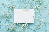 Wedding floral mockup with paper note, flowers gypsophila. Flat lay.