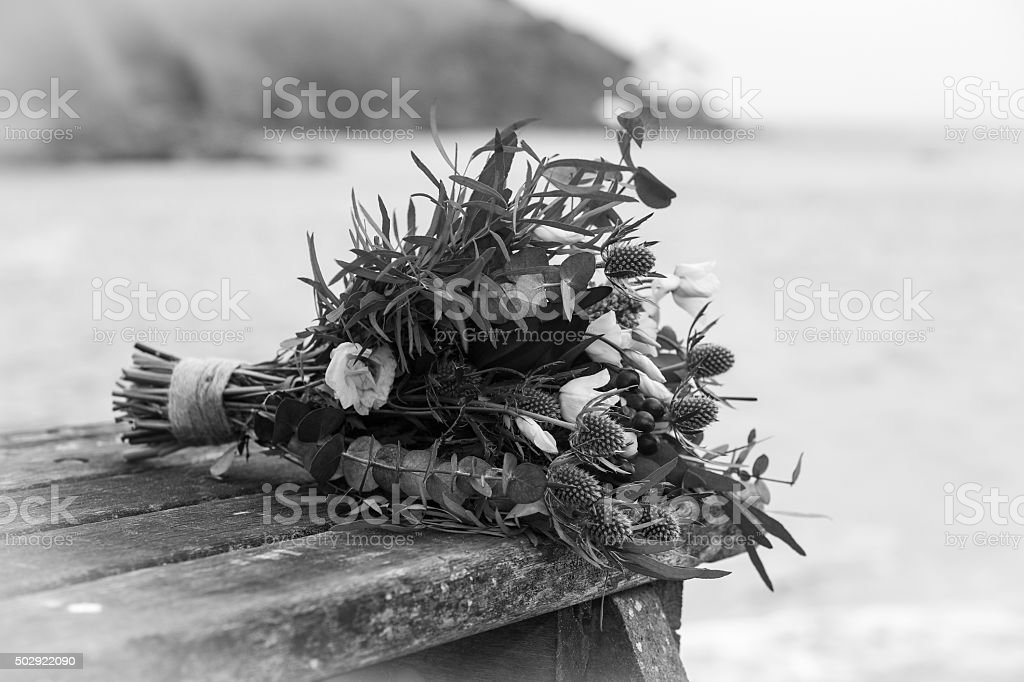 Wedding flower bouquet strung together on a wooden bench mono stock photo
